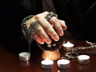 右手で水晶玉を触る女性占い師